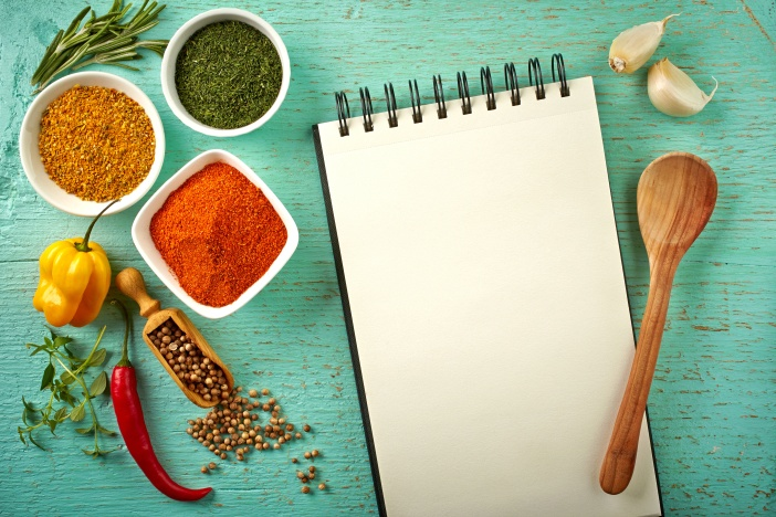 Recipe book and various spices on blue wooden background